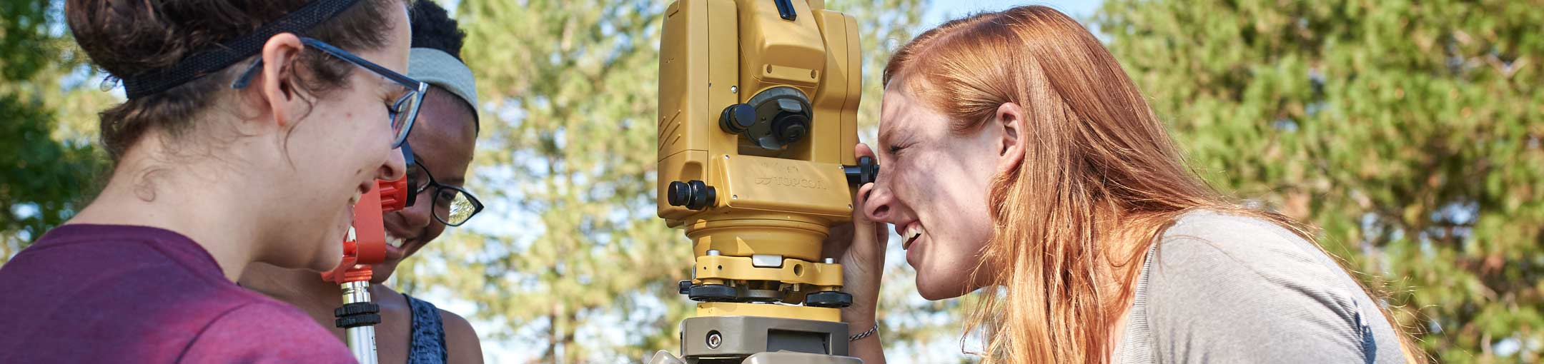Students looking through a surveying tool
