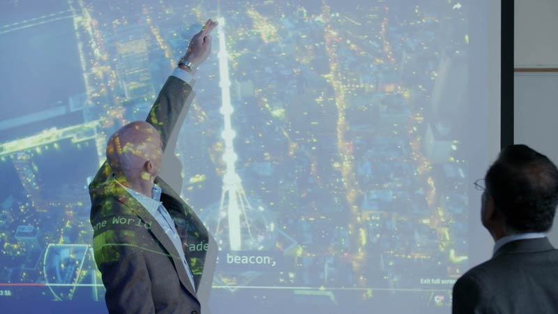 Man pointing to a map on a projector