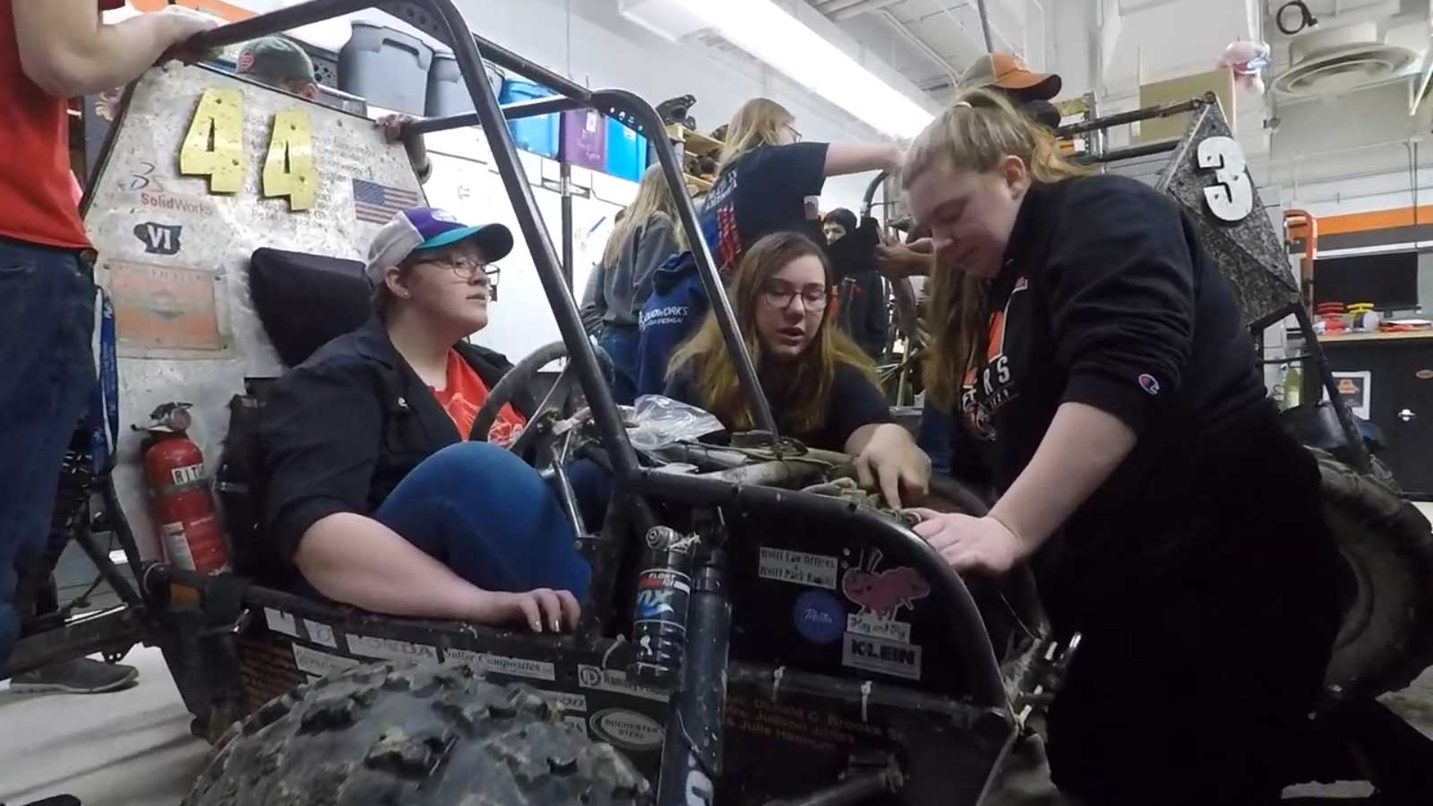 A group of students working on a small vehicle