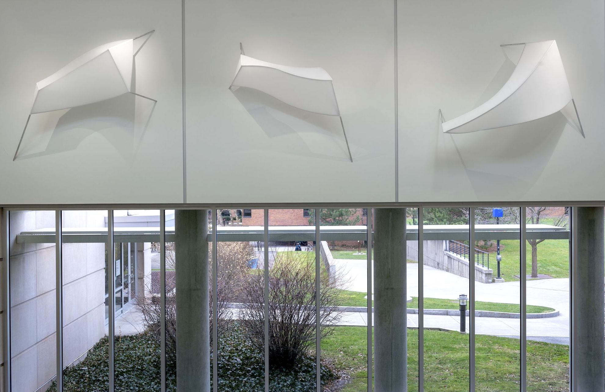 Installation of three sculptural forms made of white fabric stretched over a 3D armature and mounted on the wall.