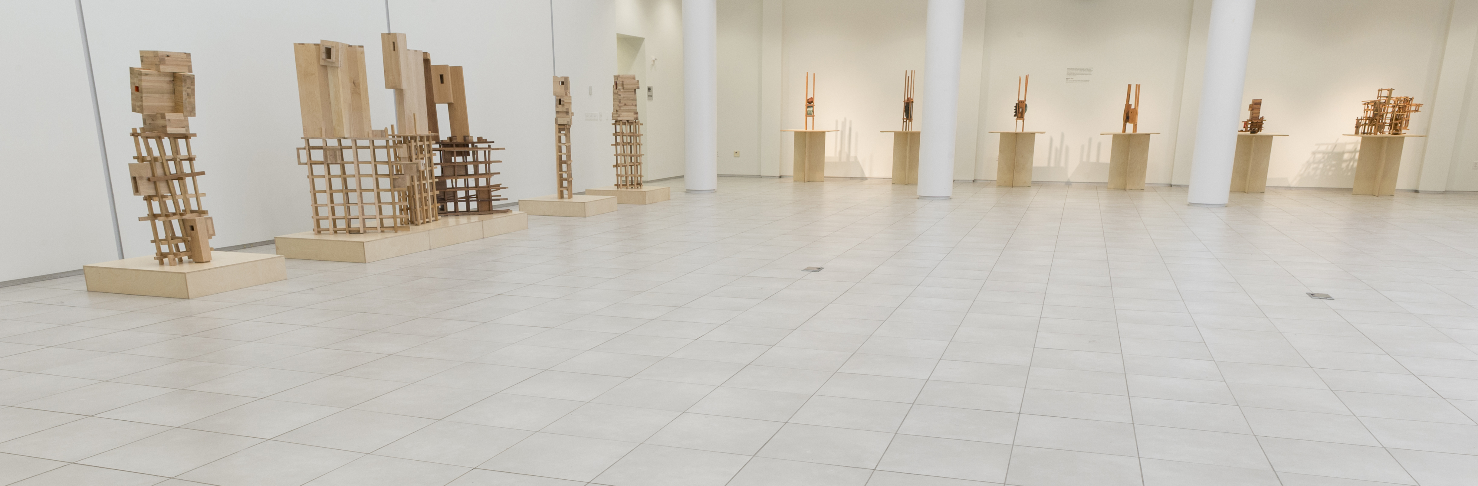 Panoramic view across gallery of series of wooden sculptures
