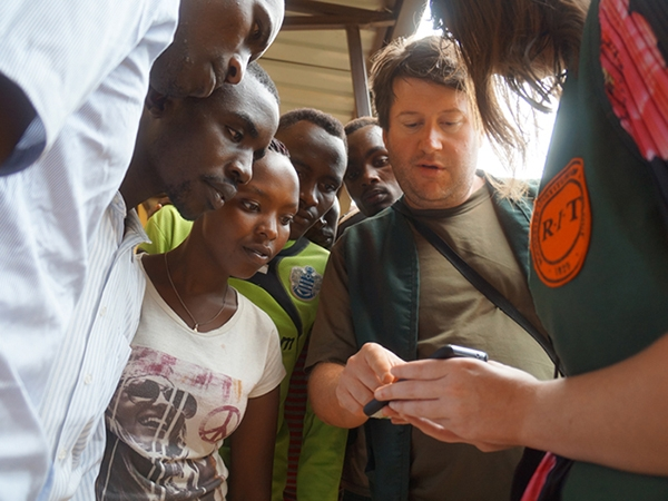 Brian Tomaszewski and an RIT student showing a mobile application to a group in Rwanda.