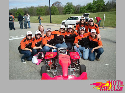 Hot Wheelz Team crouched around race car
