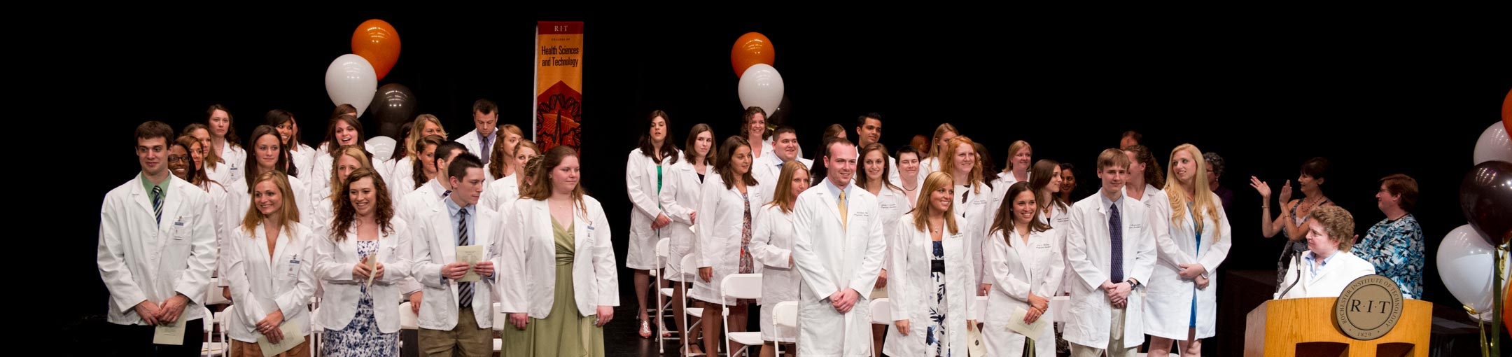 A class in white coats standing at a ceremony