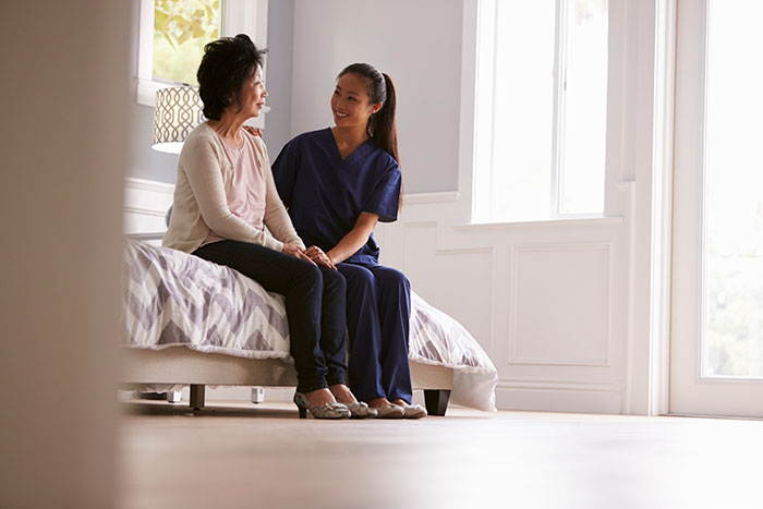 a patient and a smiling nurse sitting on a bed in a white room