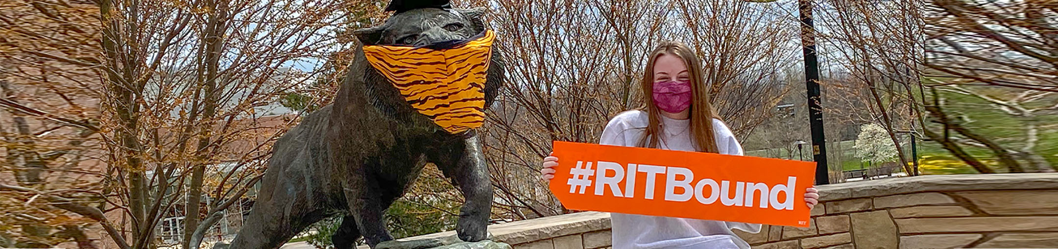 a student stands in front of the Tiger statue (both wearing masks) with a #RITBound sign
