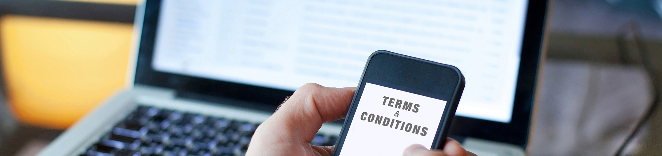 hands hold a cell phone with Terms & Conditions in front of a laptop