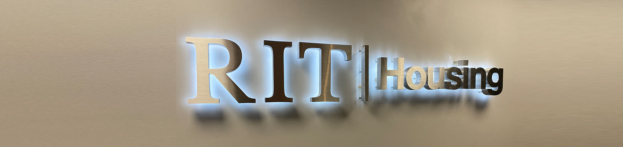 Illuminated RIT Housing Logo on a wall