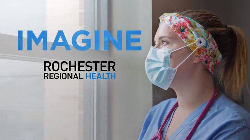 Medical worker in scrubs looking out the window with the word Imagine overlayed on it. The Rochester Regional Health logo appears underneath the word Imagine.