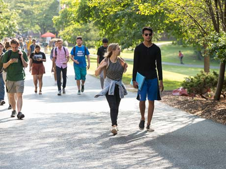 Students walking through campus on a sunny day under the shade of trees