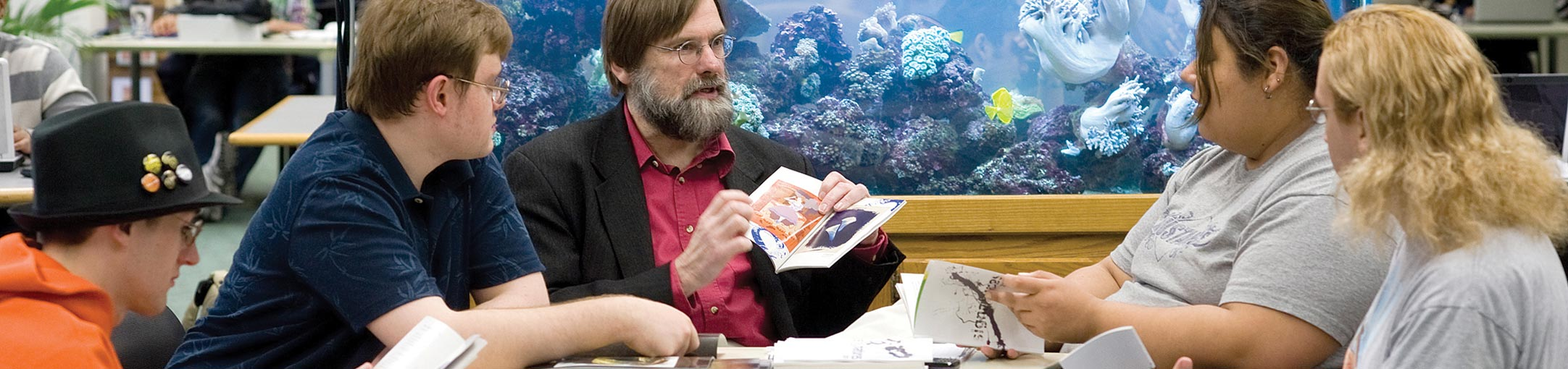 A professor sitting with a small group of students with an aquarium behind him