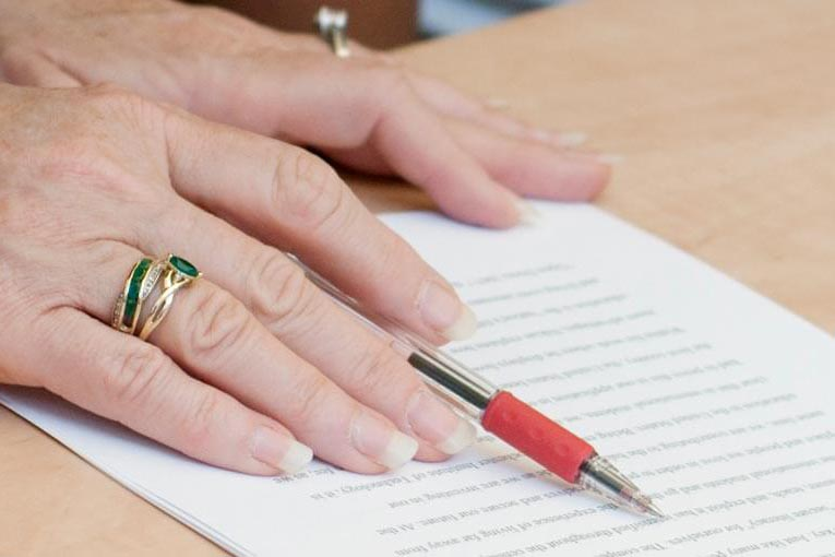 A set of hands reviewing a paper with a red pen