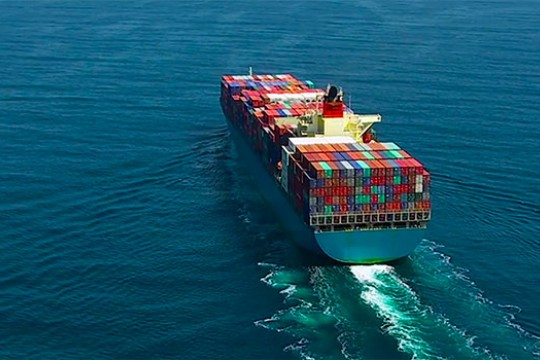 An aerial view of a large cargo ship sailing across open ocean.
