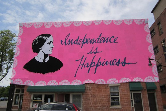 Pink banner with image of Susan B. Anthony that reads: Independence is Happiness