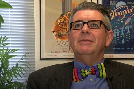 Professor with glasses and colorful bowtie sits in office