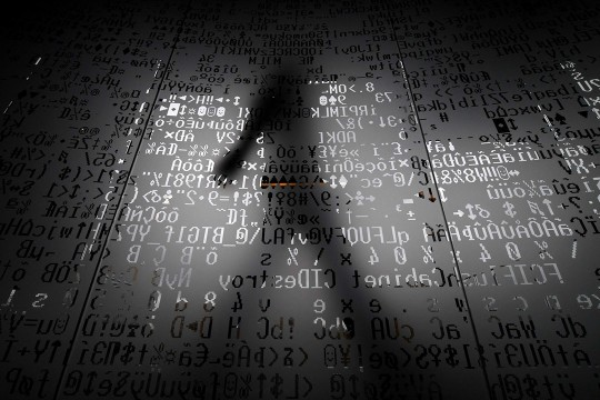Graphic of shadow of person walking by overlay of HTML code