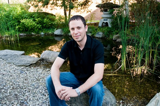 Man sits on rock near pond and garden.