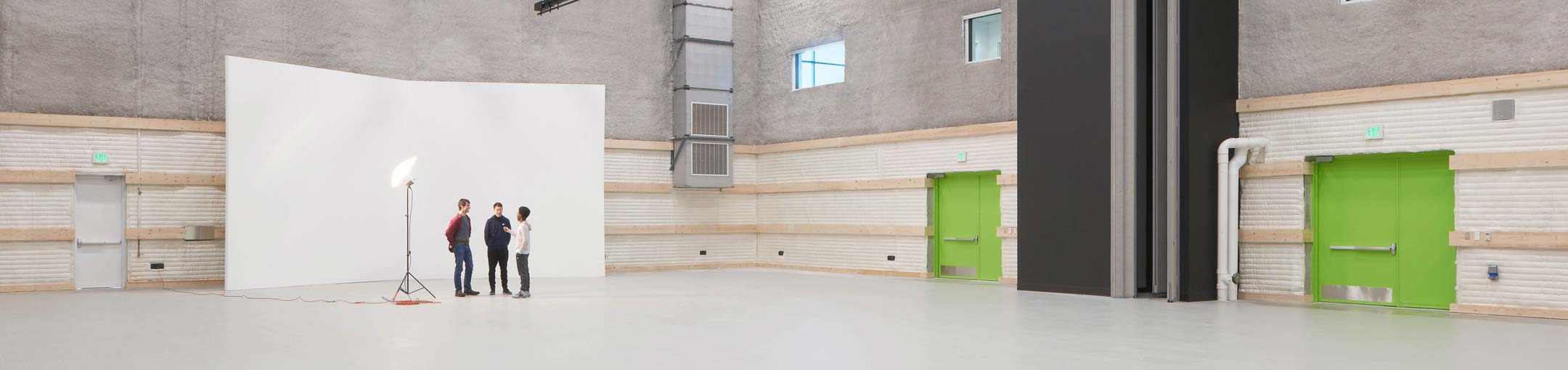 A large, open room with a white backdrop for photography with bright green doors