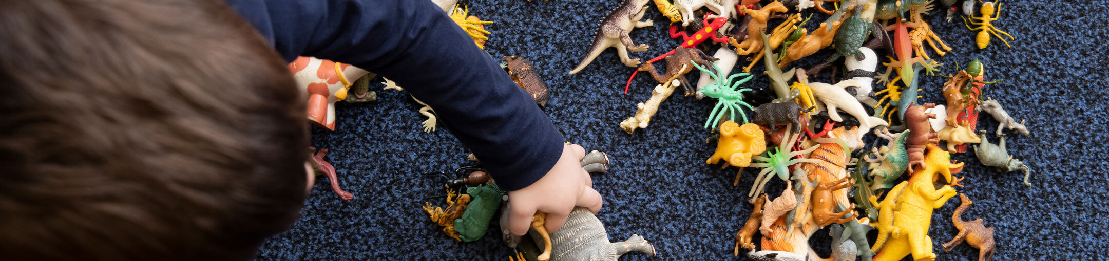 A toddler playing with a dinosaur toys on the floor.