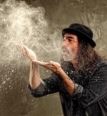 Peter Cook, wearing a fedora, blows a cloud of dust out of his hand.