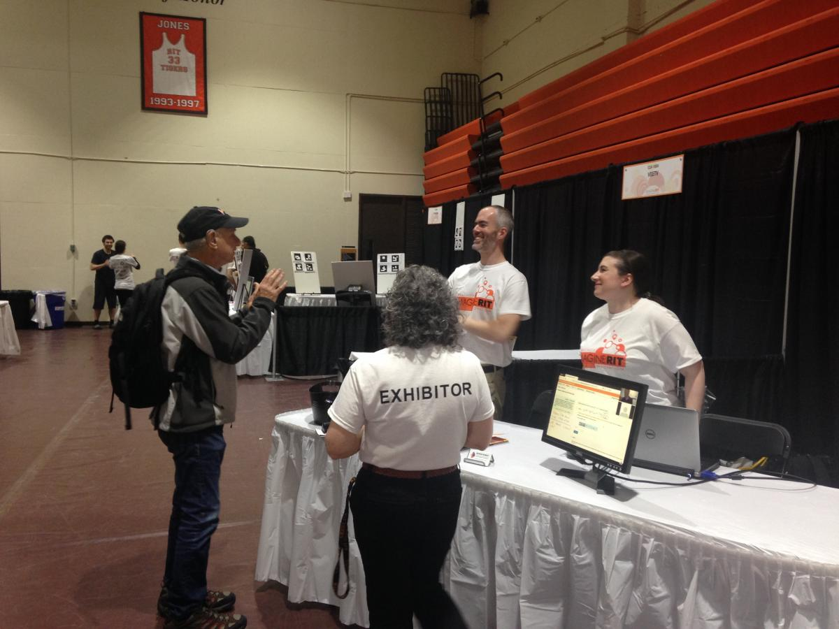Two DHHVAC staff talking to Imagine RIT guest.