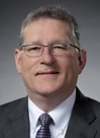 Headshot of Jeff  McCaw, glasses, grey hair, suit and tie