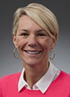 Headshot of Brandi  Rarus, short blond hair, pink sweater over white open collar shirt