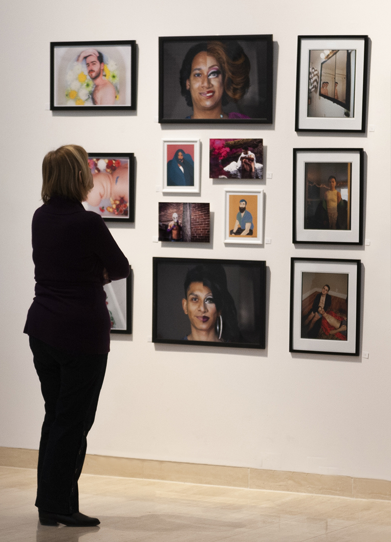 Photo of woman at looking at wall of art works.