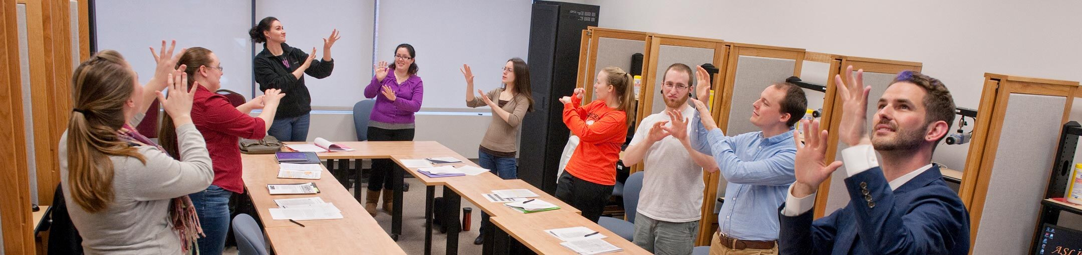 Photo of students in classroom all recreating the sign demonstrated by the instructor