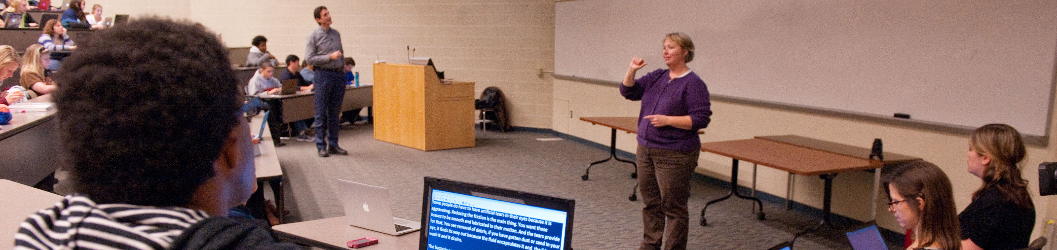 A student using access services views captions of a lecture on a laptop, while an interpret signs the lecture