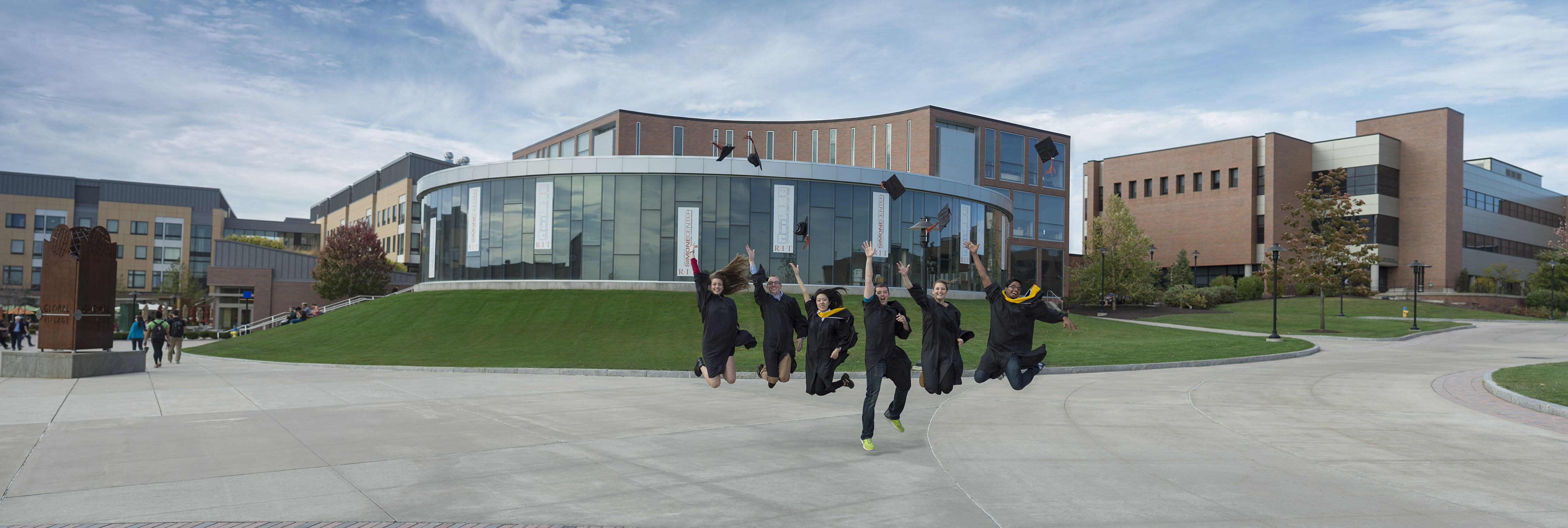 Students in caps and gowns jumping in air on campus