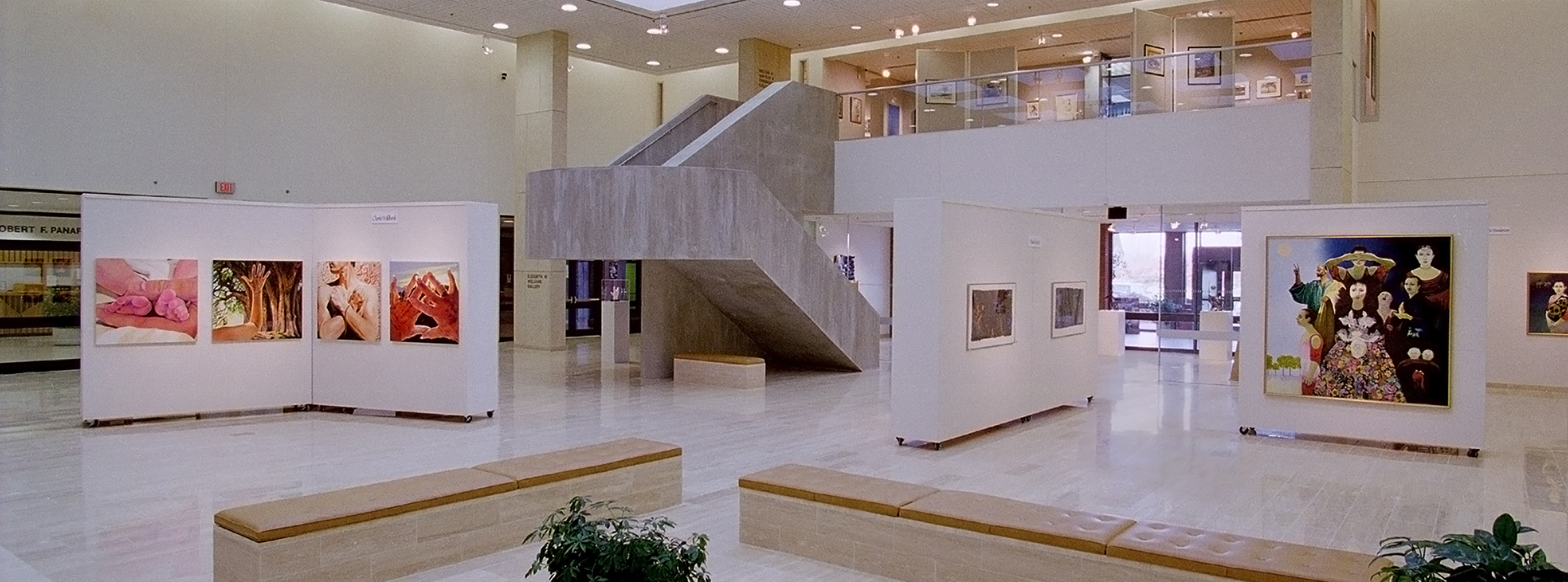 Photo of Dyer Arts space showing exhibits on moveable walls, large cement staircase, lighted ceiling