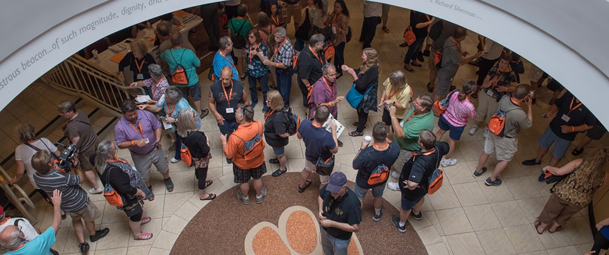 Overhead shot of alumni standing near the tiger paw print floor in the SDC lobby