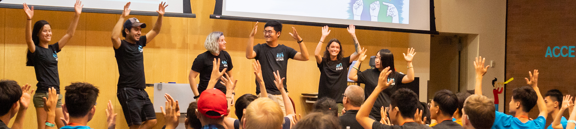 Students and instructors in auditorium with their hands up signing