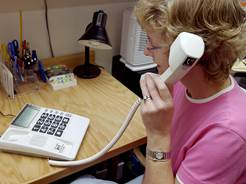 Woman using a captioned telephone