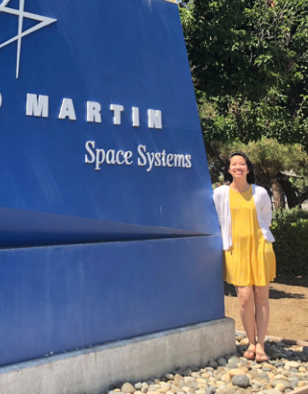 Photo of Amanda Bui, young woman with dark hair, wearing yellow dress and white sweater, standing by Lockheed Martin sign.