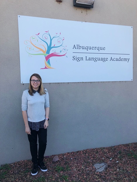 Photo of Malia Christenson, young woman with long dark blond hair, glasses, grey sweater dark pants and sneakers, standing in from of Sign Language Academy sign