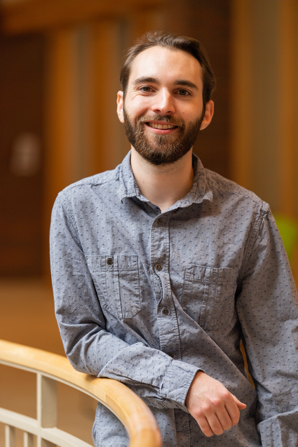 Photo of young man with dark hair and beard, smiling, wearing light blue shirt and leaning on round stair banister