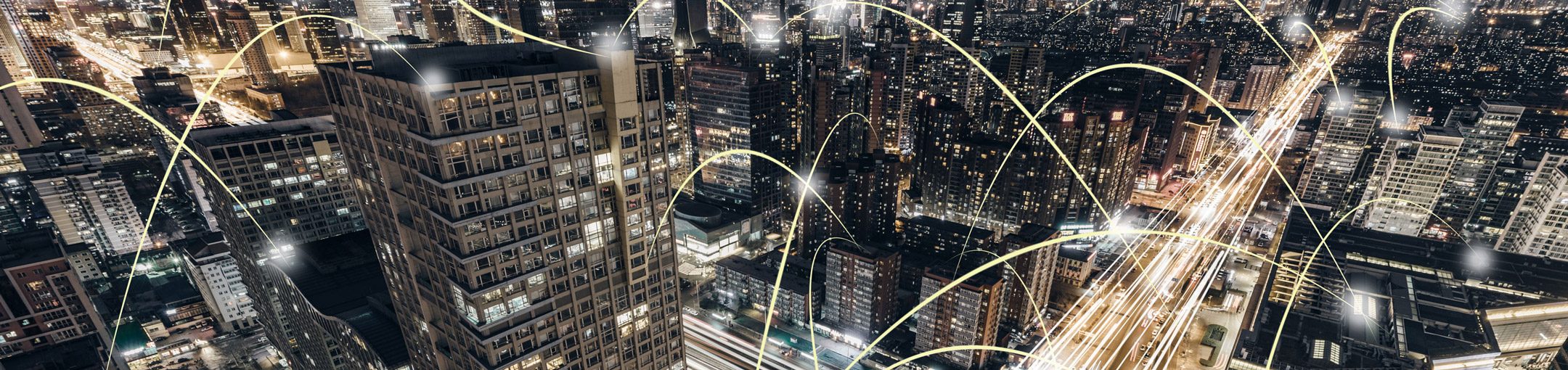 An aerial view of a city at night, with added on curved lines of light hopping from place to place.