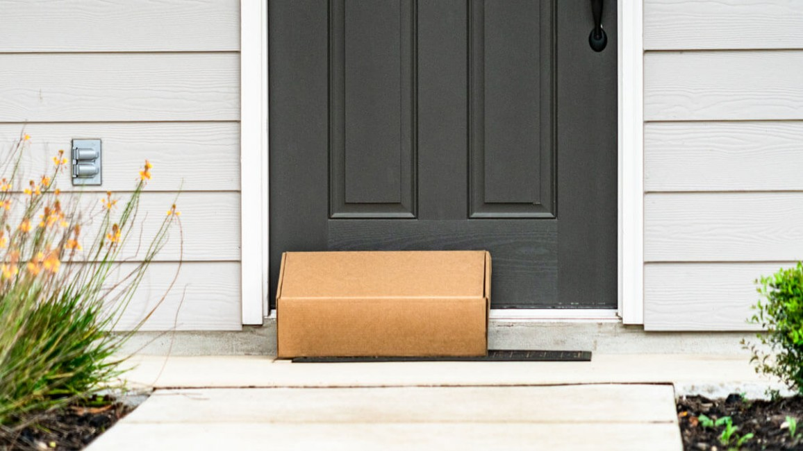 A brown mail package sits on a welcome mat in front of a door.