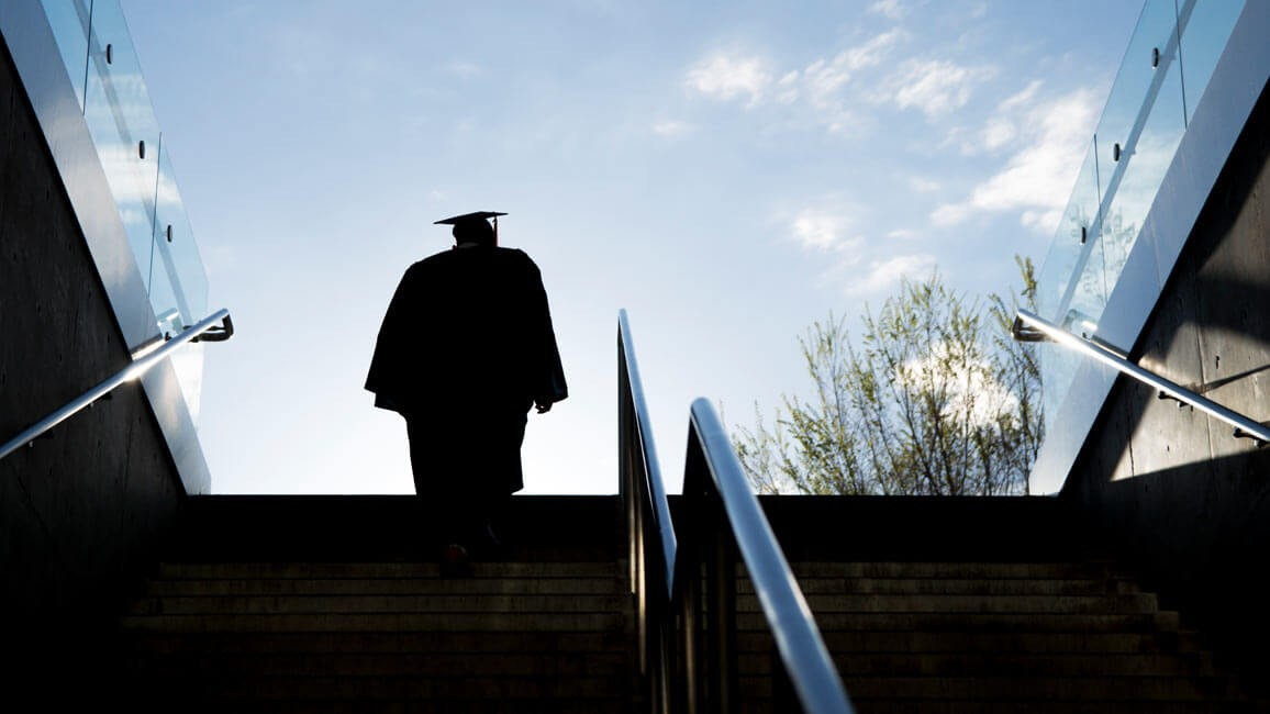 A silhouette graduating in regalia walks up a staircase.