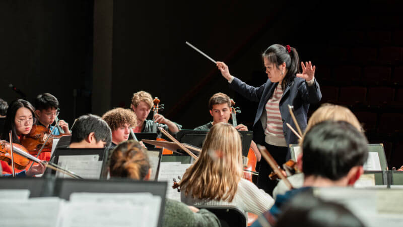 Yunn-Shan Ma conducting a piece of music played by the RIT Philharmonic Orchestra during a rehearsal.