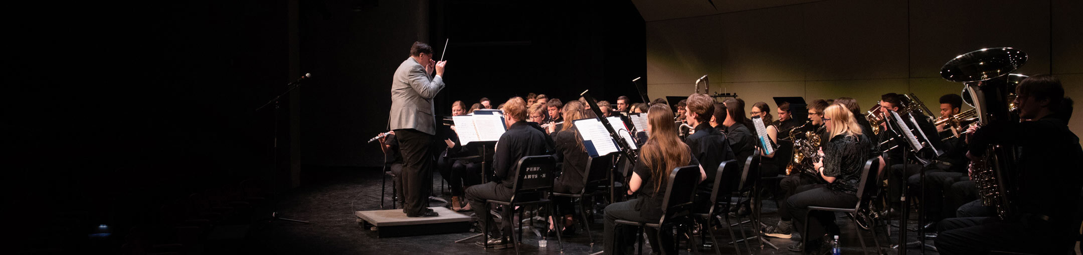 A music director conducting a piece of music played by the RIT Concert Band.