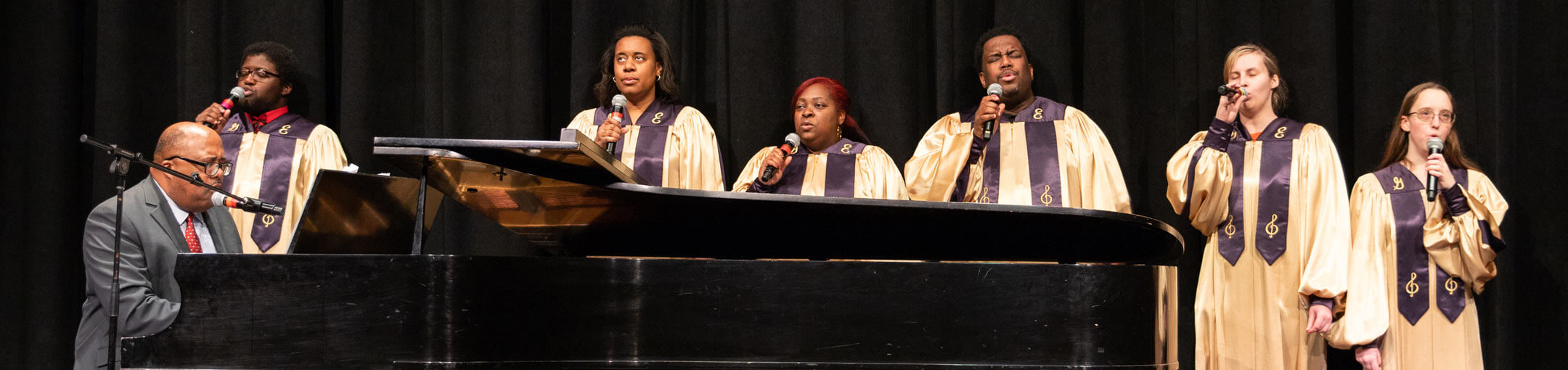 RIT's Gospel ensemble, performing on stage with Wardell Lewis playing the piano.