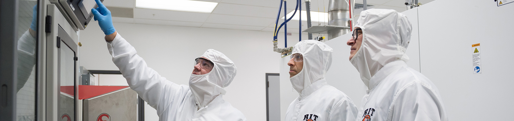 3 people in a clean room wearing white protective suits.