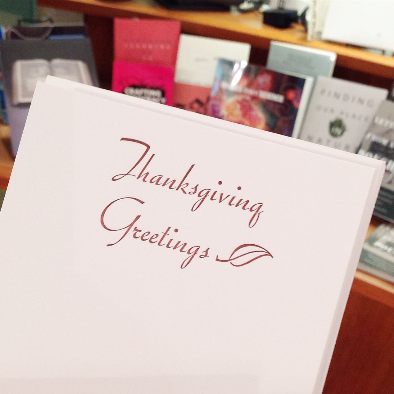 "Greeting card with the text ""Thanksgiving Greetings."" Book display in background."