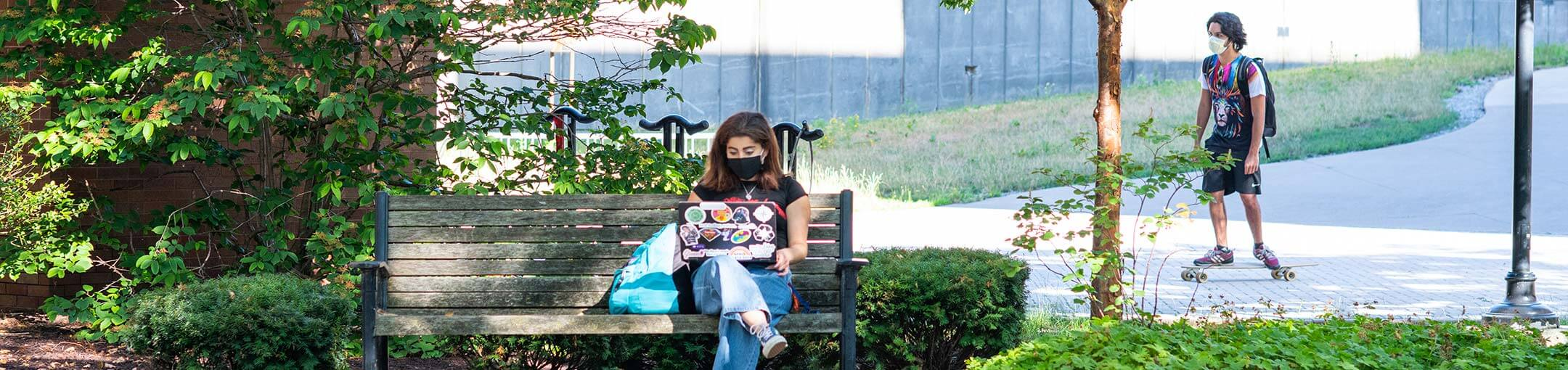 A student sits outside on a bench under a tree.