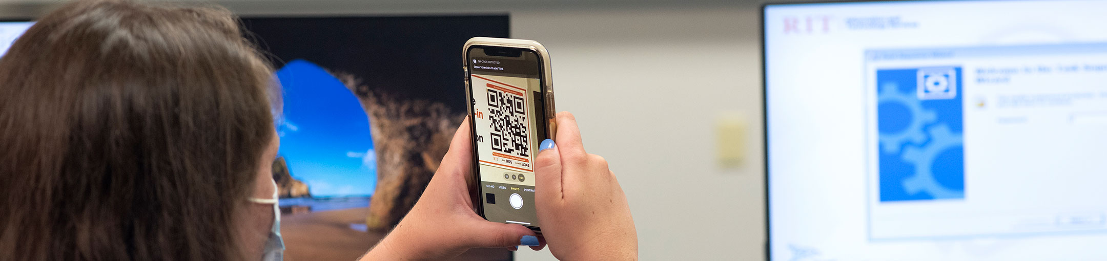 Student wearing a mask scanning a QR code on her phone