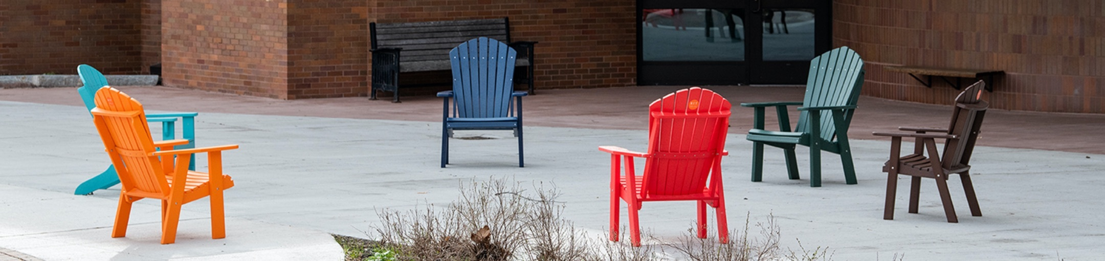 six Adirondack chairs spaced out outdoors.