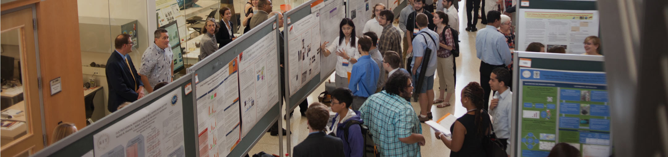 Participants and attendees of a previous Undergraduate Research Symposium viewing various exhibits.